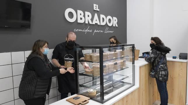EL OBRADOR, DE LA COCINA A CASA Arriba, una trabajadora del Obrador revisa un guiso con la cocinera, Lourdes Arilla, al fondo. En la foto de abajo, una clienta recogiendo su comida.
