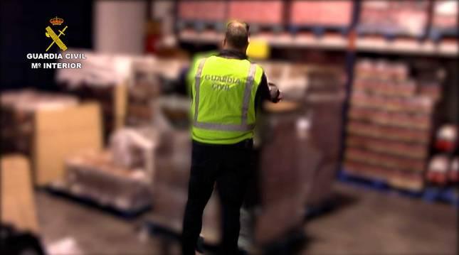 Un guardia civil examina una de las cajas de botellas de ron falsificadas