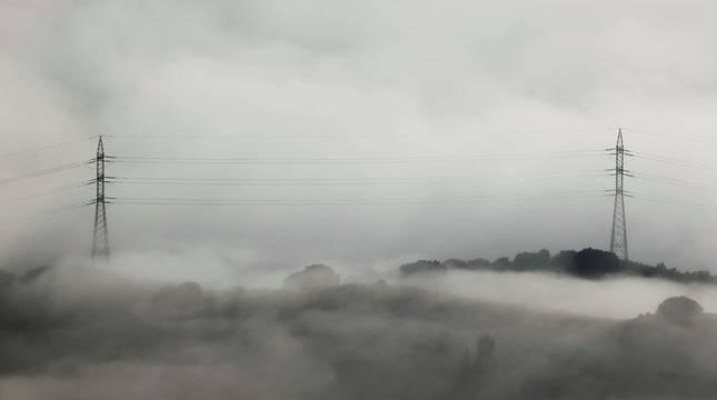 Dos torres del tendido eléctrico quedan casi cubiertas por las nubes en el alto de El Perdón en una jornada en la que las nieblas de primeras horas de la mañana han sido la nota característica.