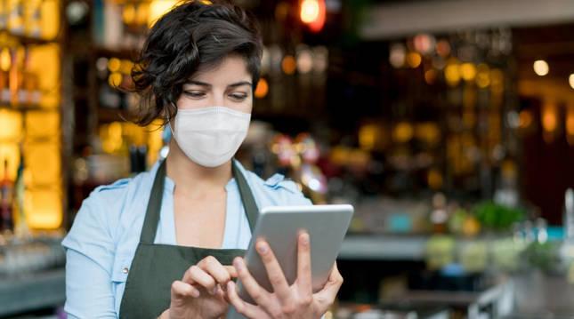 Una hostelera cionsulta una aplicación en su tablet.