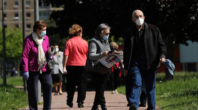 Varias personas pasean mayores por un parque.