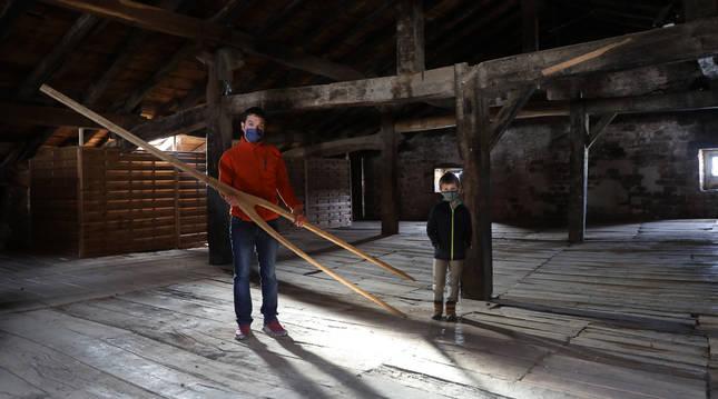 Junto a su hijo, Tasio, en el 'sabai' o desván de la posada, Rubén Beunza Erice sostiene el 'bigo' o esqueleto de Miel Otxin.