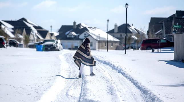 Un hombre camina sobre la nieve en Pflugerville,Texas.