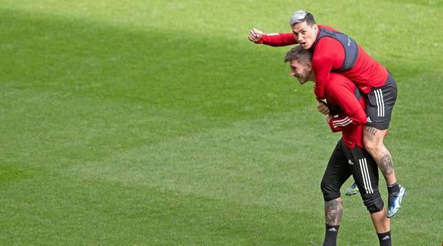 El Chimy Ávila subido en la espalda de David García en los instantes previos de la sesión de ayer en el estadio de El Sadar.