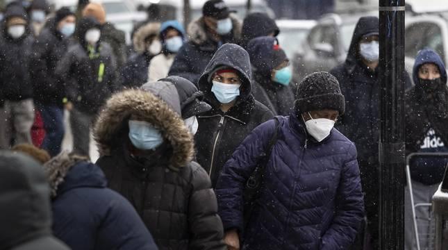 Un grupo de personas camina con mascarillas en el barrio de Queens, en Nueva York.