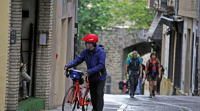 Foto de varios peregrinos a pie y en bicicleta, a su paso por Pamplona en la ruta del Camino de Santiago.