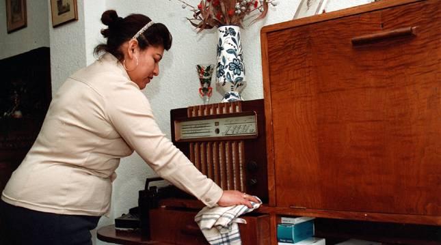 Una empleada de hogar limpia el polvo de un mueble.