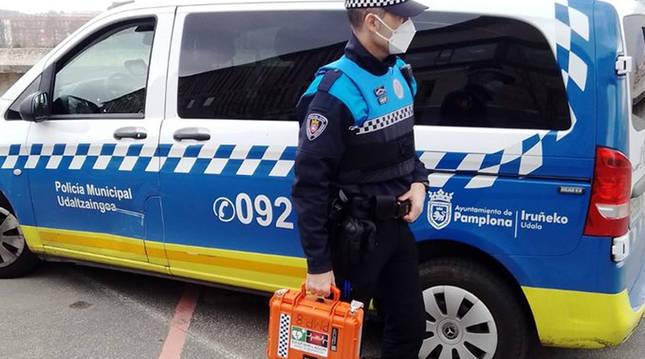 Un policía municipal sujeta un equipo portátil de desfibrilador.