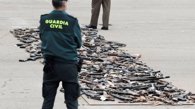 Un Guardia Civil observa los de varios centenares de armas incautadas en décadas pasadas a las bandas terroristas ETA y GRAPO antes de ser destruidas durante el acto celebrado en la Academia de la Guardia Civil de Valdemoro (Madrid).