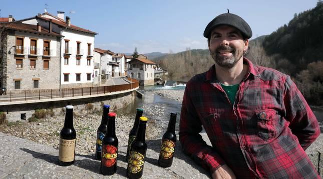 Jox Ubau Galarza, en el puente de Burgui, con la cerveza que elaboran en el pueblo.