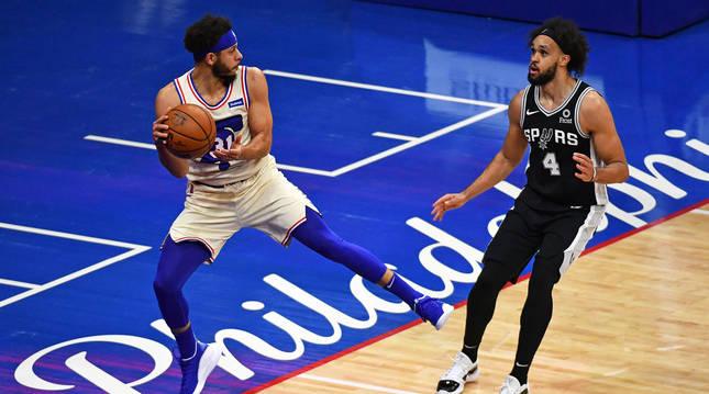 Seth Curry, de Philadelphia, trata de dar un pase ante el jugador de los Spurs,Derrick White.