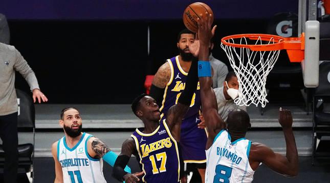 El jugador de Lakers Dennis Schroder busca la canasta entre al defensa de Charlotte Hornets