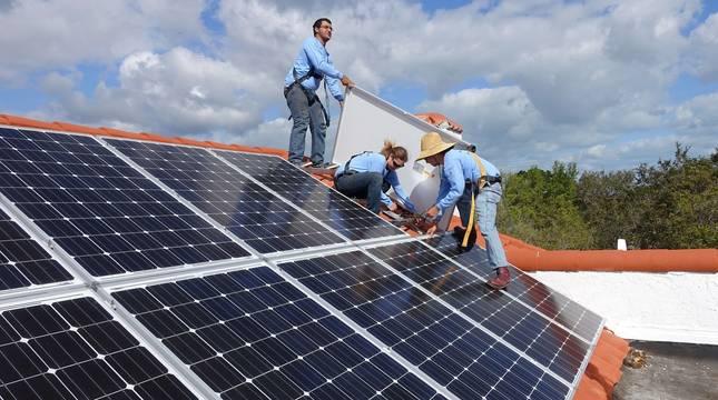 Trabajadores instalan placas solares en el tejado de una vivienda.