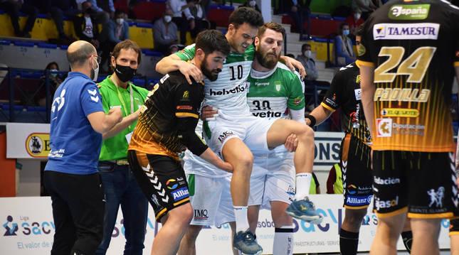 Juan Del Arco (izda.) y Javier García ayudan a salir de la cancha a Ander Torriko tras sufrir la lesión.
