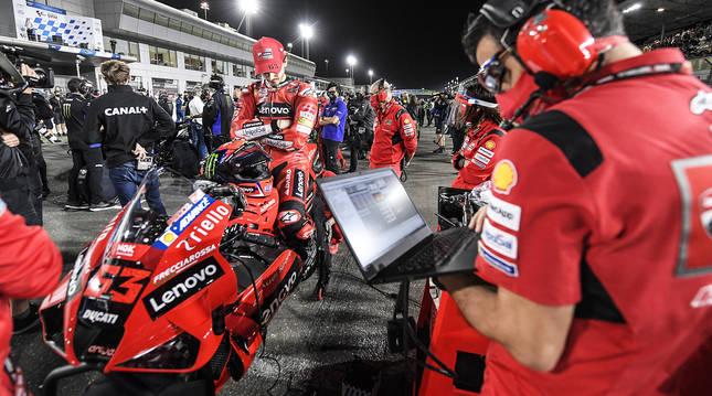 El italiano Franceso Bagnaia se concentra sobre su Ducati antes de salir desde la primera plaza en el GP de Catar 2021.
