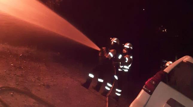 Efectivos de Bomberos de Navarra lanzan agua sobre las llamas del incendio en el monte Lerro.