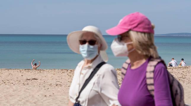 Dos mujeres caminan por el paseo marítimo de la playa de Palma de Mallorca.