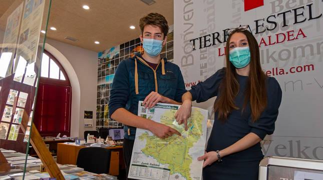 Foto de los técnicos de la oficina de Turismo, en la plaza de la Coronación, muestran un mapa de la comarca.
