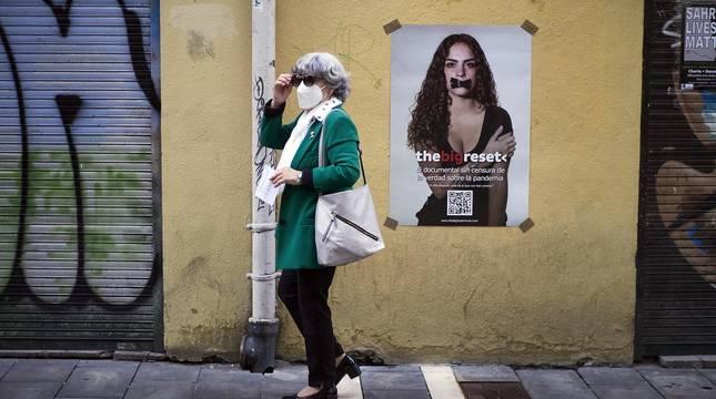 Una mujer pasea con mascarilla por el Casco Antiguo de Pamplona en Jueves Santo.