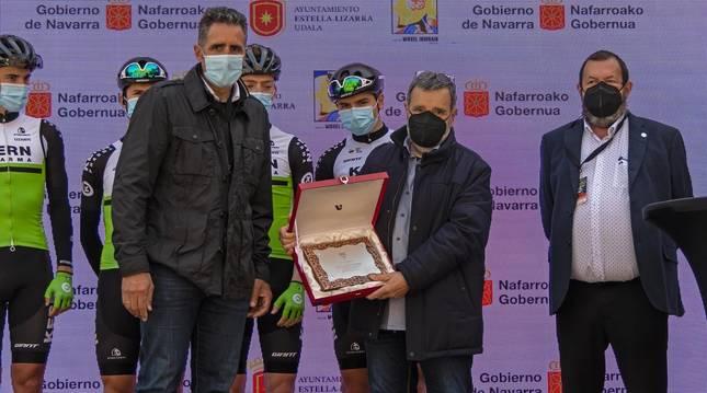Manolo Azcona, flanqueado por Miguel Induráin y Miguel Ángel García Mitxelena, con su equipo Kern Pharma al fondo, ayer en la salida de Estella.