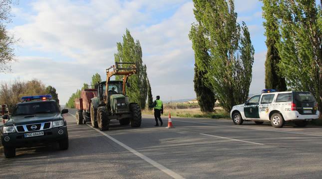 Un tractor pasa ante el control de la Guardia Civil en el acceso a Arguedas desde Tudela.