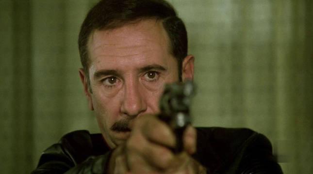 Germán Areta (Alfredo Landa) apunta a uno de los atracadores en la primera escena de la película El Crack.