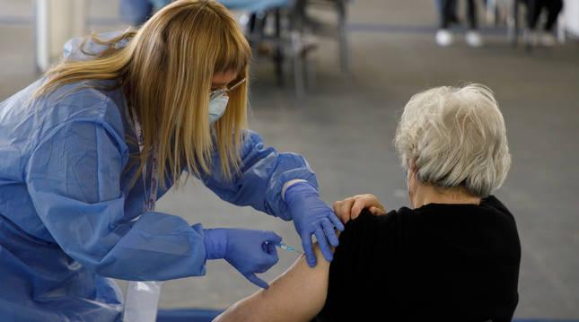Una sanitaria inyecta una vacuna de AstraZeneca a una mujer