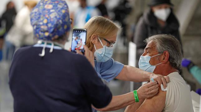 Un hombre recibe una dosis de vacuna en el Wizink Center de Madrid.