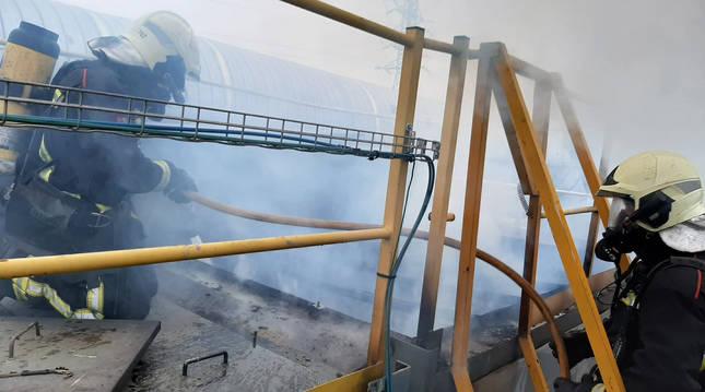Dos efectivos de Bomberos de Navarra trabajan en la zona afectada de la fábrica Mapsa, en Orkoien.