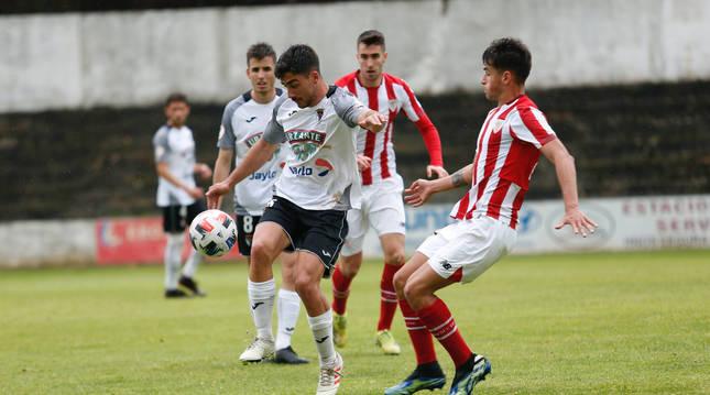 Gualda, del Tudelano, disputa un balón con Beñat Prados, del Bilbao Athletic, en el partido disputado en el Ciudad de Tudela.