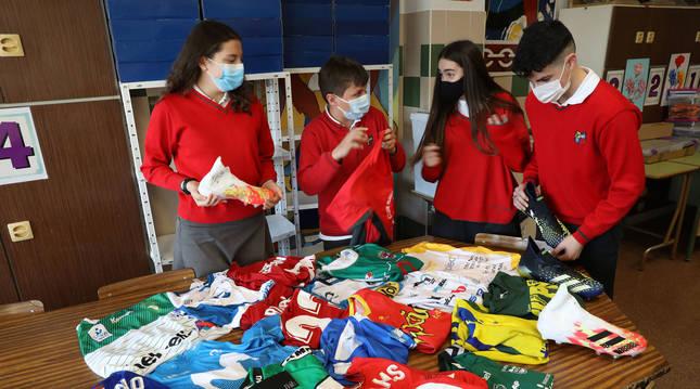 Foto de algunos de los alumnos encargados de llevar a cabo el proyecto miran el material deportivo que será sorteado.