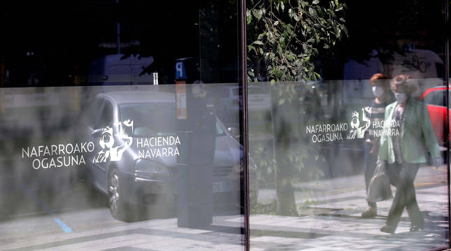 Foto de dos personas reflejadas en el cristal de la oficina de Hacienda en la calle Esquiroz de Pamplona.