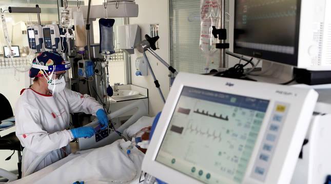 Una enfermera de la UCI del Complejo Hospitalario de Navarra atiende a un paciente.