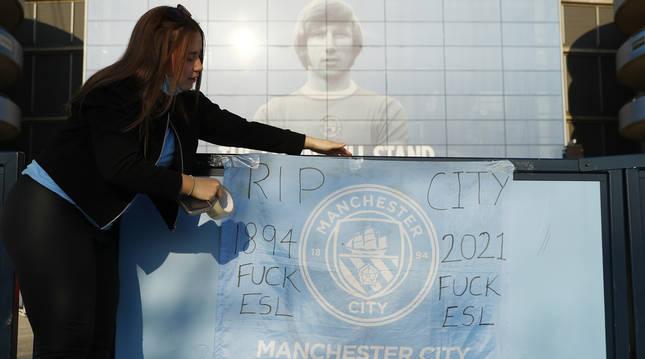 Una aficionada del City coloca una bandera con un mensaje crítico con la Superliga europea.