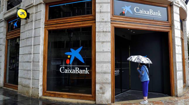 Una mujer que observa el interior de la sede de Caixabank en la plaza del Ayuntamiento de Valencia.