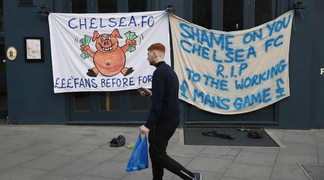 Un aficioando pasa por delante de dos pancartas contrarias a la Superliga europea a las puertas de Stamford Bridge