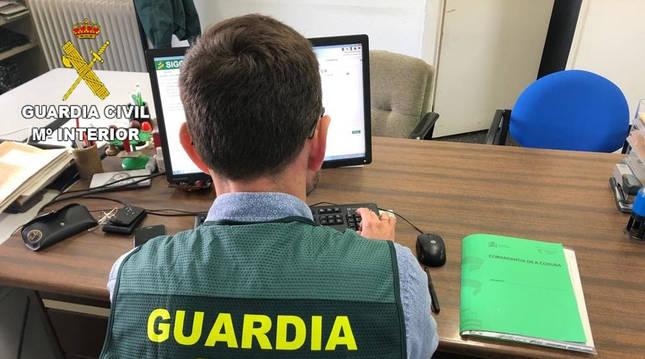 Un Guardia Civil investiga delitos informáticos en un ordenador.