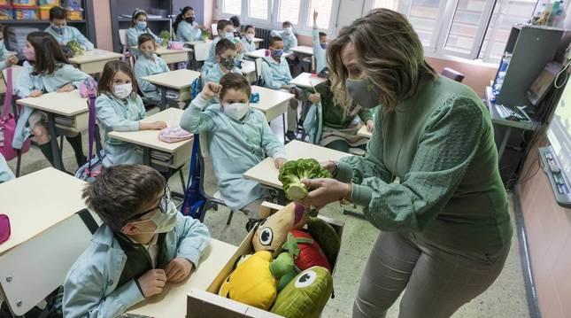 Foto de Ana Berdonces, de la empresa FHF, muestra un brócoli a alumnos del colegio Anunciata de Tudela.