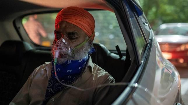 Un enfermo con un respirador en un coche, en la India.