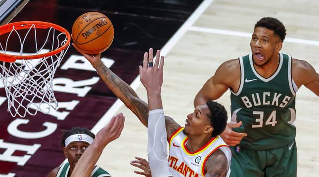 Lou Williams, de los Hawks, entra a canasta entre la defensa de lso Bucks.