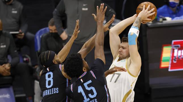 Luka Doncic trata de superar a dos defensas de Sacramento Kings.