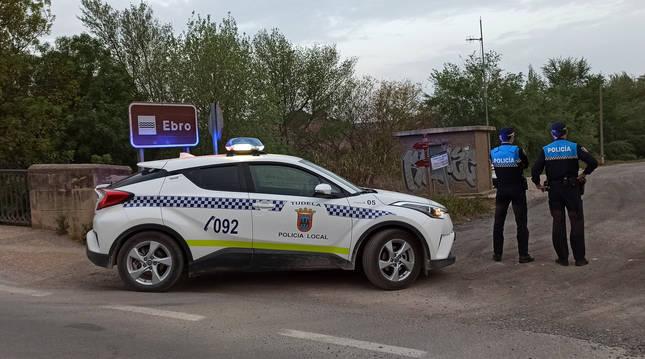 Dos agentes de la Policía Local de Tudela junto al coche patrulla en una vigilancia anterior.