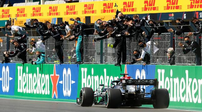 Hamilton cruza la línea de meta con su equipo celebrándolo en la valla.
