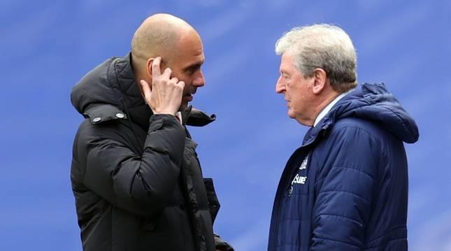 Pep Guardiola conversa con el técnico del Crystal Palace, Roy Hodgson, antes del encuentro de la Premier del fin de semana.