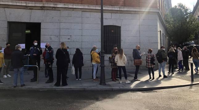 Votantes esperan una larga cola a las puertas del IES Cardenal Cisneros en Madrid.