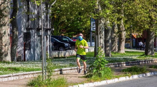 Un runner corre por una calle de Vitoria cubierto con una mascarilla.