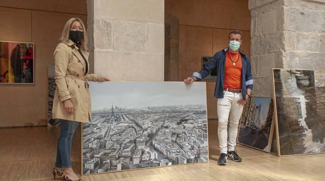 Foto del pintor navarro Albert Sesma y la concejal de Cultura de Reocín, Eva Cobo, con uno de los cuadros de la muestra.