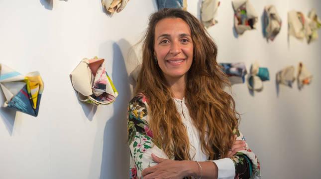 La artista pamplonesa Carla Querejeta posa delante de varias de sus obras, a las que denomina 'esculturas textiles', en la sala La Puerta Gótica, del Colegio Mayor Belagua