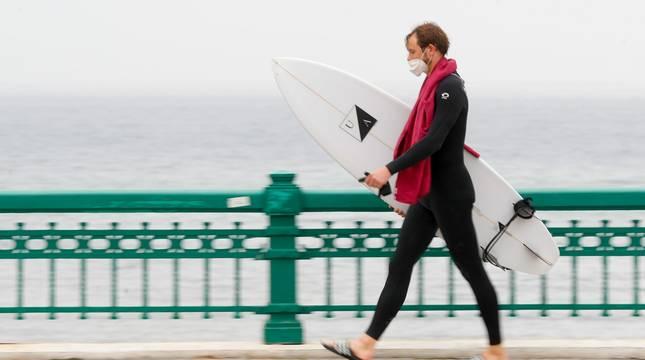 Un surfista camina junto a la playa de la Zurriola de San Sebastián el pasado mes de abril.