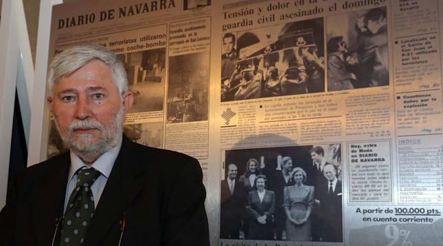 Foto de Florencio Domínguez ante uno de los paneles que muestran portadas de Diario de Navarra con atentados de ETA en la exposición del Palacio del Condestable.